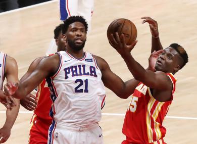 The Atlanta Hawks' Clint Capela, right, grabs a defensive rebound away from the Philadelphia 76ers' Joel Embiid.