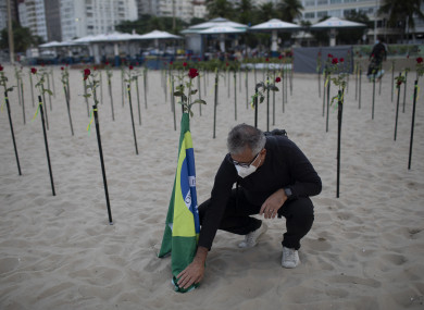 An man places a Brazilian national flag in the sand on Copacabana beach during a protest against the handling of the pandemic