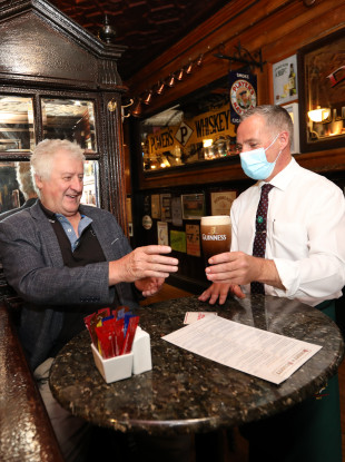 Jim Whelan with a pint of Guinness from barman Damian Ellis in Doheny and Nesbitt pub in Dublin.