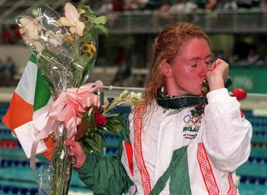 Ireland's Michelle Smith kisses her gold medal at the side of the Olympic swimming pool after winning the 100m freestyle.