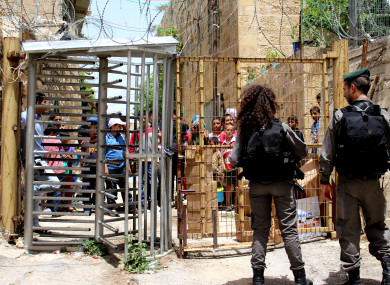 Two Israeli soldiers at a checkpoint in Hebron with Palestinian children on the other side of the fence