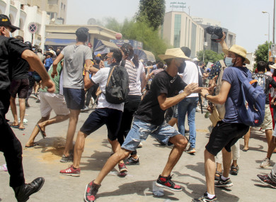 A Tunisian police officer scuffles with protesters during a demonstration in Tunis, Tunisia, Sunday,