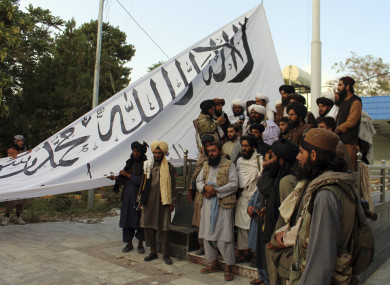 Taliban fighters raising their flag at the Ghazni provincial governor's house in southeastern Afghanistan yesterday.