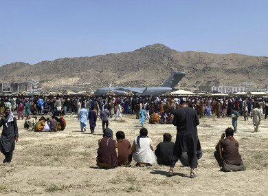 Hundreds of people gather near a U.S. Air Force C-17 transport plane at a perimeter at the international airport in Kabul, Afghanistan.