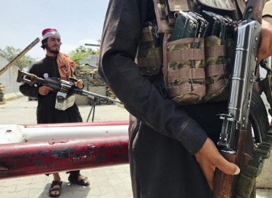 Taliban fighters stand guard at a checkpoint near the US Embassy that was previously manned by American troops, in Kabul, on Tuesday.