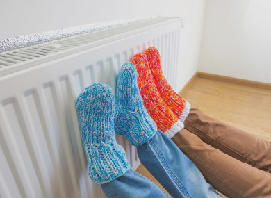 People warming themselves at a radiator (file photo)